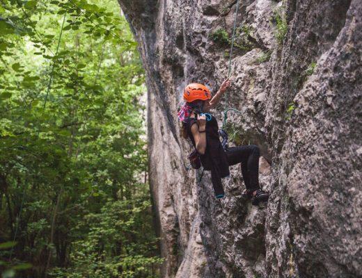 man in black shirt climbing on gray rocky mountain during daytime